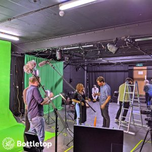Wide of a studio, greenscreen setup on the left, crew are discussing the next shot.