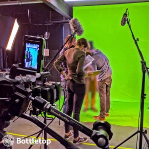 Green screen setup with camera in the foreground, actor's costume is being adjusted.